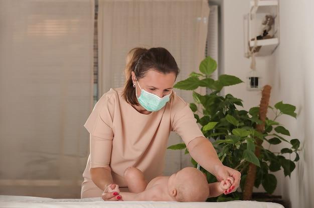 Женщина делает массаж новорожденному в медицинской маске. Premium Фотографии