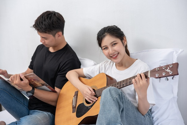 앉아있는 여자는 기타와 책을 들고 노래하는 남자를 재생합니다. 무료 사진
