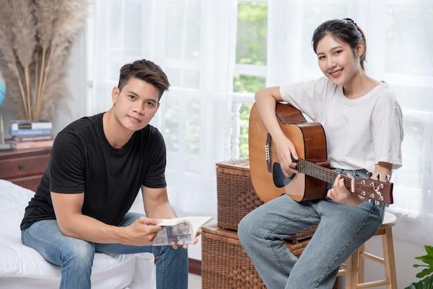Сидящая женщина играет на гитаре, а мужчина держит книгу и поет. Бесплатные Фотографии