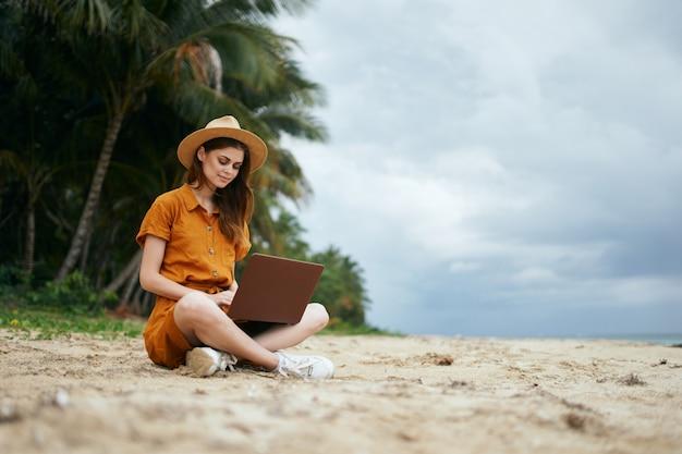 ヤシの木のある砂に沿って海に沿ってラップトップを持って旅行する女性 Premium写真