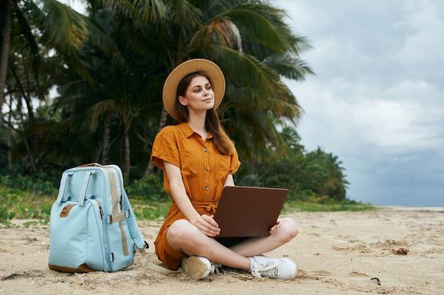 ヤシの木が砂に沿って海に沿ってラップトップを持って旅行する女性 Premium写真