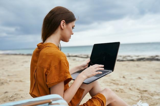 海を望むビーチでラップトップを使用している女性 Premium写真