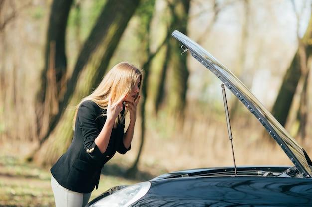 Женщина ждет помощи возле своей сломанной машины на обочине дороги. Бесплатные Фотографии