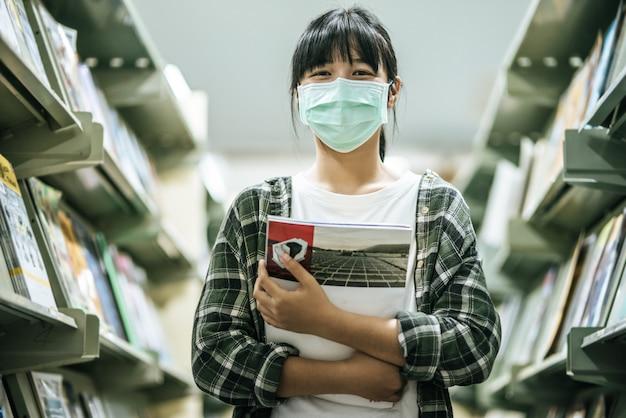マスクをして図書館で本を探している女性。 無料写真
