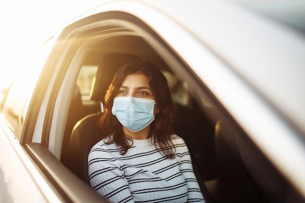 開いている窓の外を横向きに見ている後部座席のタクシー車で医療用滅菌マスクを着用している女性 Premium写真