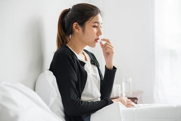 Женщина, которая плохо себя чувствует на кушетке и собирается принимать антибиотики. Бесплатные Фотографии