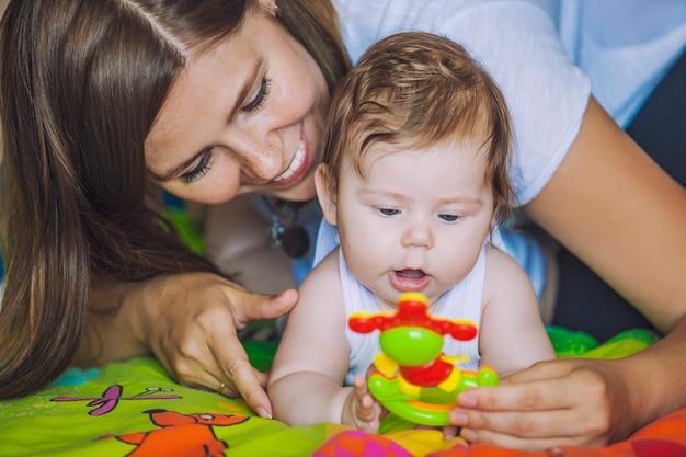 아기를 둔 여성이 눈앞에서 화려한 장난감을 놀아 발달하고 관심을 끌기 위해 프리미엄 사진