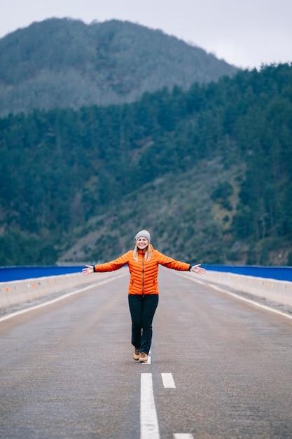 Женщина с шерстяной шапкой и оранжевым пальто бежит и прыгает по дороге с горами на заднем плане Premium Фотографии