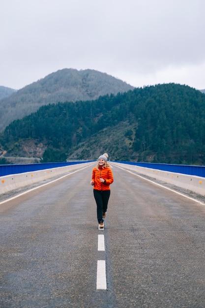 ウールの帽子とオレンジ色のコートを着た女性が走り、山を背景にした道を飛び降りる Premium写真