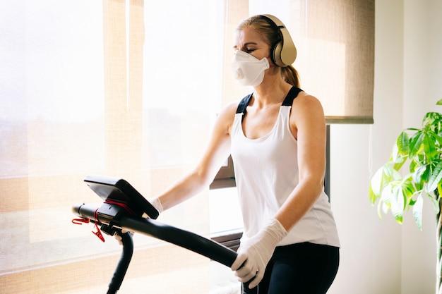 マスクと手袋のスリムなアスリートの女性がトレッドミルで実行されている自宅で運動をします Premium写真