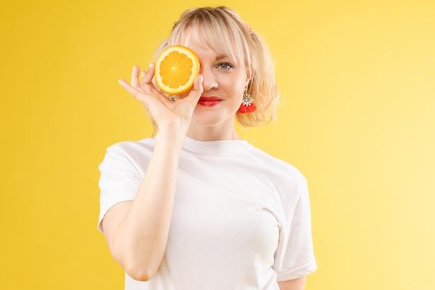 Женщина с апельсинами в глазах. красная помада губ. веселая, жизнерадостная  девушка источает позитивные, испорченные апельсины. изолированные на желтом  фоне | Премиум Фото
