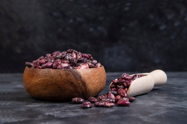 黒に乾燥豆の生の穀物でいっぱいの木製のボウル 無料写真
