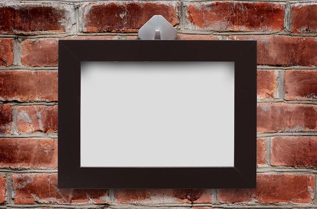 茶色のレンガの壁に木枠が掛かっている Premium写真