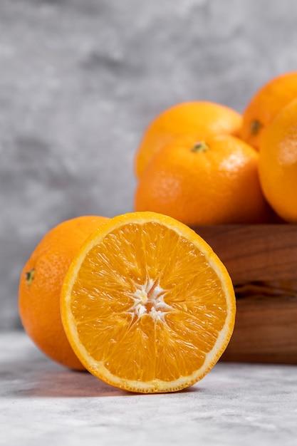 Деревянная старая коробка, полная целых и нарезанных апельсиновых фруктов, помещенная на мрамор Бесплатные Фотографии
