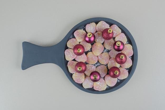 Деревянная тарелка, полная желейных конфет в форме сердца с елочными шарами. Бесплатные Фотографии