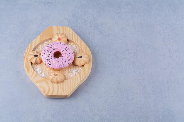 甘いクッキーとおいしいピンクのドーナツの木のプレート。 無料写真