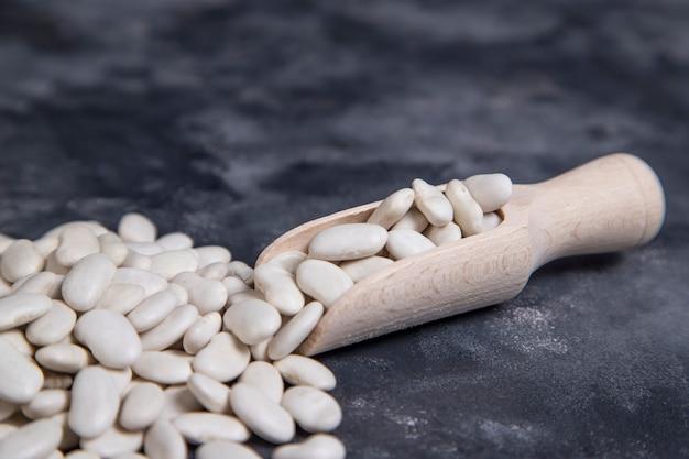 돌 위에 놓인 마른 버터 콩이 가득한 나무 숟가락 무료 사진
