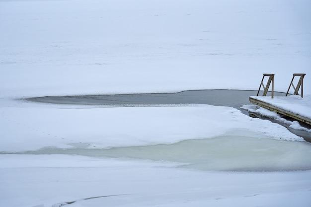 얼음 구멍으로 이어지는 나무 계단. 프리미엄 사진