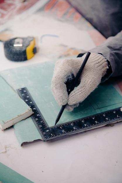검은 색 연필로 장갑을 끼고있는 작업자가 눈금자에 따라 보드의 치수를 취소합니다 프리미엄 사진