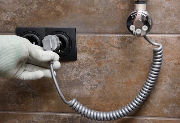 Рабочий устанавливает нагревательный элемент в полотенцесушитель в ванной. Premium Фотографии