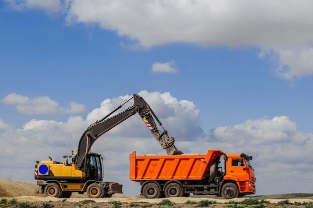 Желтый экскаватор-погрузчик загружает землю в грузовик во время строительства дороги. Premium Фотографии