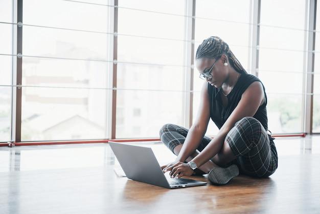 若いアフリカ系アメリカ人女性はラップトップコンピューターに満足しています。 無料写真