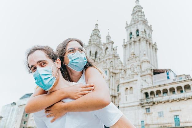 Молодая и счастливая пара в масках перед древним собором во время путешествия Premium Фотографии