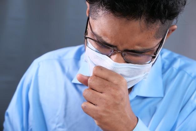Молодой азиатский мужчина с защитной маской на лице грустит Premium Фотографии