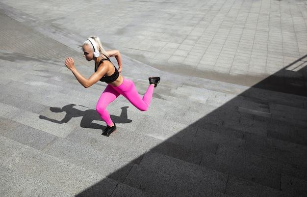 Молодая спортивная женщина в рубашке и белых наушниках работает, слушая музыку на улице на открытом воздухе. Бесплатные Фотографии