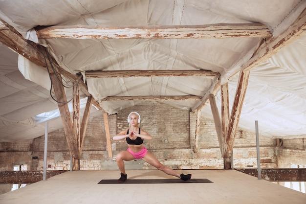 버려진 건설 현장에서 음악을 듣고 운동 셔츠와 흰색 헤드폰에 젊은 체육 여자. 스쿼트 만들기. 건강한 라이프 스타일, 스포츠, 활동, 체중 감량의 개념. 무료 사진