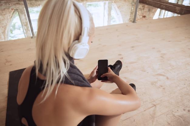 버려진 건설 현장에서 음악을 듣고 밖으로 작동하는 흰색 헤드폰에 젊은 운동 여자 무료 사진