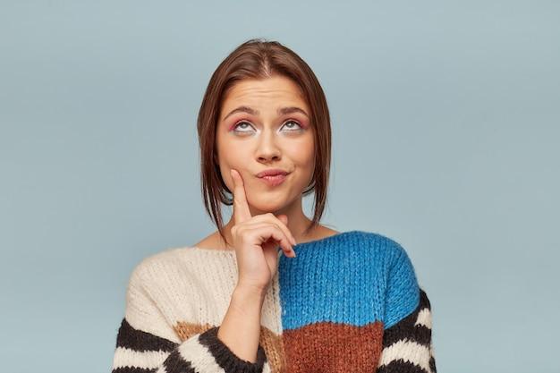 Молодая привлекательная женщина с красивым макияжем, одетая в разноцветный свитер, задумчиво держит палец возле щеки. Бесплатные Фотографии
