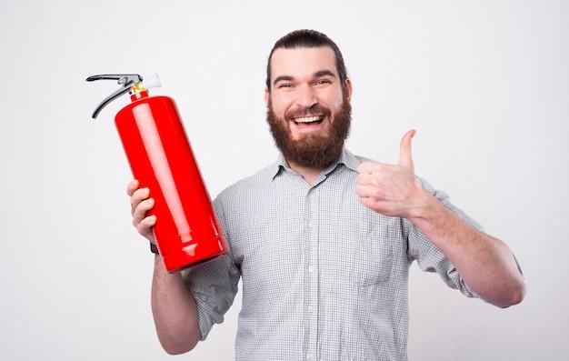 Молодой бородатый мужчина смотрит и улыбается в камеру, держа огнетушитель и большой палец вверх возле белой стены Premium Фотографии