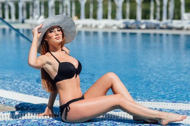 Молодая красивая шатенка в черном купальнике, солнцезащитные очки у бассейна у воды Premium Фотографии