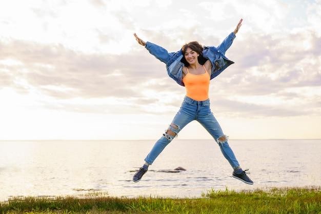 Молодая красивая девушка в джинсовой куртке, джинсах и желтой футболке прыгает на фоне моря в летний день, позирует на закате Бесплатные Фотографии