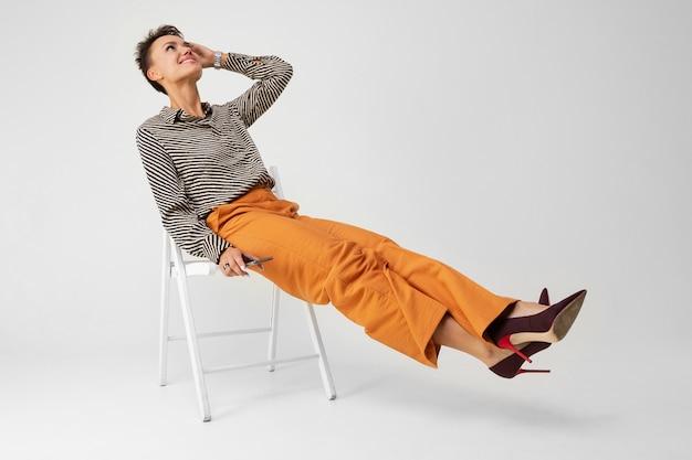 Молодая красивая девушка с короткими темными волосами, косметикой в черно-белой полосатой рубашке, коричневых брюках и туфлях сидит на стуле с телефоном в руках и думает. Premium Фотографии
