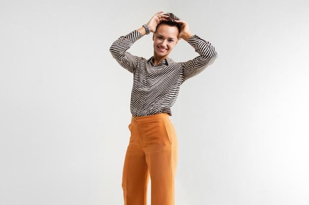 Молодая красивая девушка с короткими темными волосами, макияж в черно-белой полосатой рубашке, коричневые брюки и туфли стоит и улыбается. Premium Фотографии