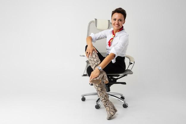 Молодая красивая девушка с короткими темными волосами, макияж в белой рубашке, черные брюки, длинные кожаные змеиные сапоги, с красным шарфом, наручными часами и красивым макияжем сидит на белом компьютерном стуле и улыбается Premium Фотографии