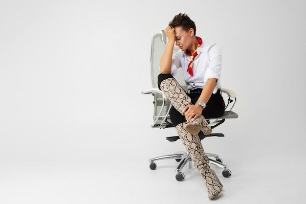 Молодая красивая девушка с короткими темными волосами, макияж в белой рубашке, черные брюки, длинные кожаные змеиные сапоги, с красным шарфом, наручные часы и красивый макияж сидит на белом компьютерном стуле и думает Premium Фотографии