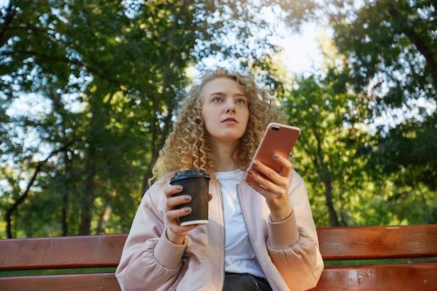 コーヒーを飲みながら公園のベンチに座っている若い美しい女性ブロンド 無料写真