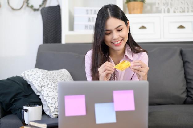 若い美しい女性が自宅でインターネットのウェブサイトでのオンラインショッピングにクレジットカードを使用して、eコマースのコンセプト Premium写真