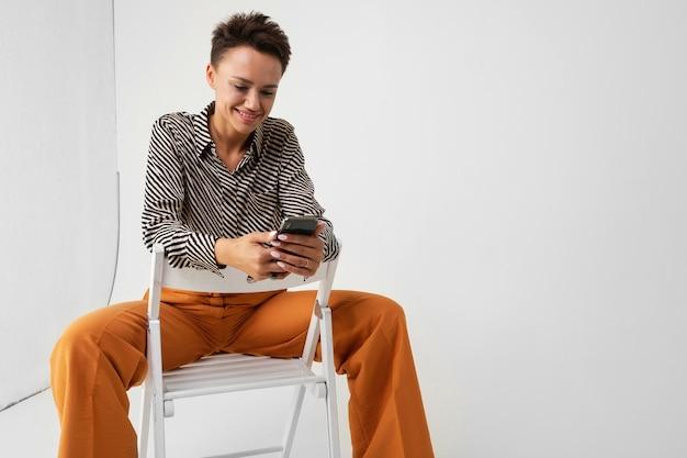 Молодая красивая женщина с короткими темными волосами, макияж в черно-белой полосатой рубашке, коричневые брюки и туфли сидит на стуле с телефоном в руках и думает Premium Фотографии