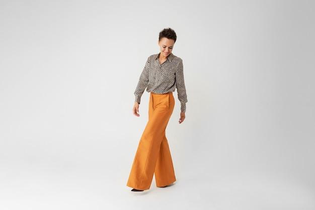 Молодая красивая женщина с короткими темными волосами, макияж в черно-белой полосатой рубашке, коричневые брюки и туфли Premium Фотографии