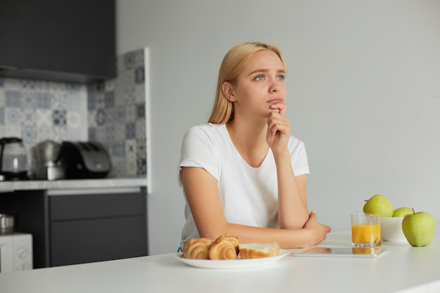 Молодая блондинка сидит за кухонным столом, грустная, задумчиво смотрит в сторону окна. Бесплатные Фотографии