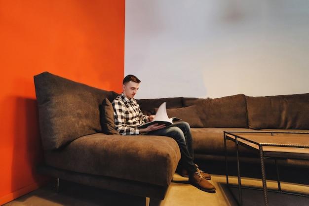 Молодой деловой человек читает бизнес-проект в стильном офисе. отдых с журналом. Premium Фотографии