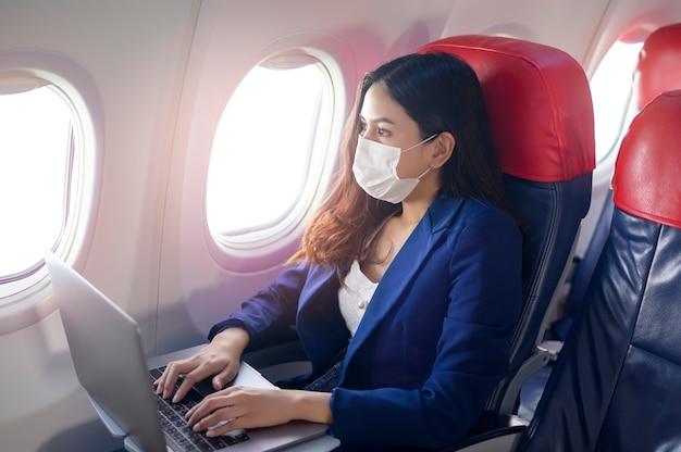 フェイスマスクを身に着けている若い実業家がラップトップを使用して、covid-19パンデミックコンセプト後の新しい通常の旅行 Premium写真