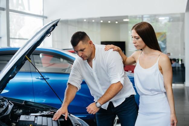 若いカップルがディーラーで新車を選び、ディーラーの担当者に相談します。 Premium写真