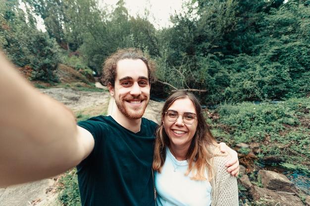 Молодая пара делает селфи в лесу, улыбаясь Premium Фотографии