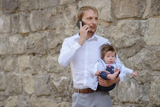 Молодой отец разговаривает по мобильному телефону и держит свою маленькую дочь на руках. копировать пространство Premium Фотографии