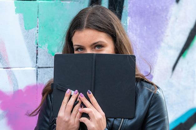 낙서가 뿌려진 벽에 기대어 그녀의 손에 검은 활을 가진 젊고 들떠있는 여성 프리미엄 사진